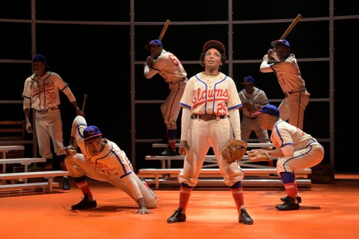 'Toni Stone' (Dawn Ursula) speaks to the audience about her passion for baseball as a team assembles behind her in Lydia R. Diamond's Toni Stone, performing at A.C.T.'s Geary Theater now through Sunday, March 29, 2020.