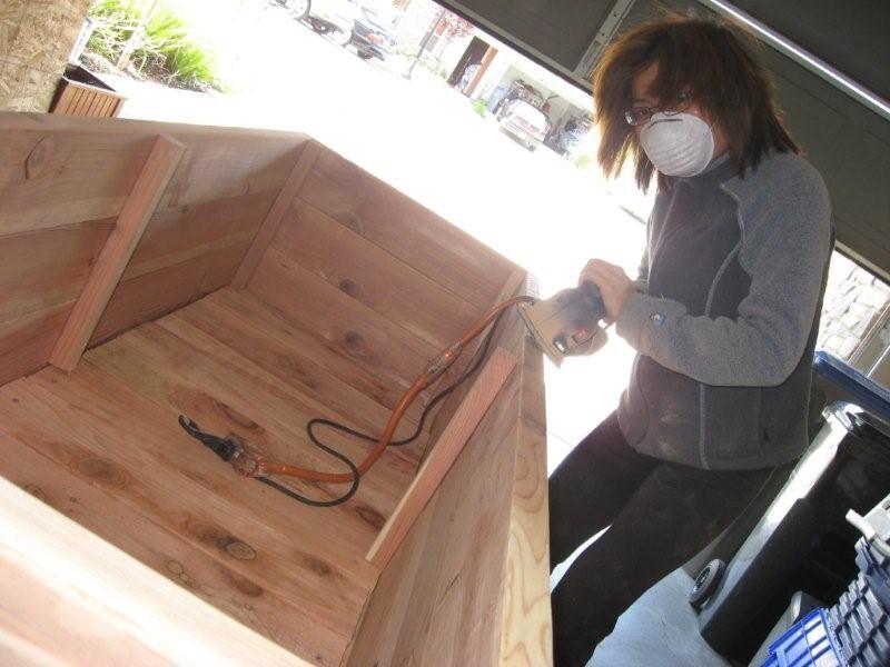 Loni Stark sanding a wooden planter box
